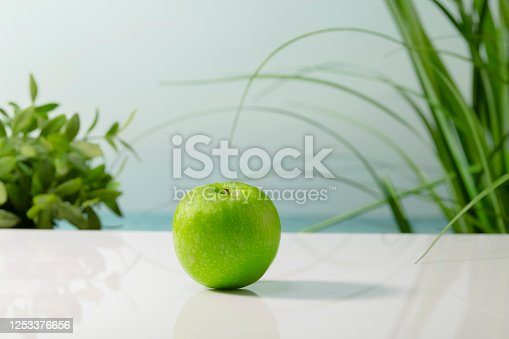 Close up of a delicious looking green apple on a table on an out of focus background. Healthy and vegan food concept.