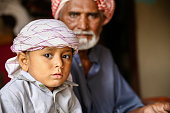 a depressed arab grand father with his young cute grandson