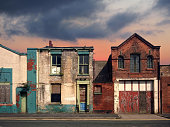 istock a deserted street of old abandoned ruined houses with bright peeling paint and crumbling brickwork in evening sunlight against a bright cloudy sunset sky redevelopment or fantasy concept 1126548660
