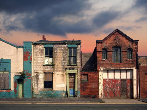 a deserted street of old abandoned ruined houses with bright peeling paint and crumbling brickwork in evening sunlight against a bright cloudy sunset sky redevelopment or fantasy concept - dilapidated stock pictures, royalty-free photos & images