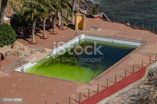 a dirty and abandoned pool with green water, scary pool, dyrty waterl, abandoned swimming pool, ruined pool