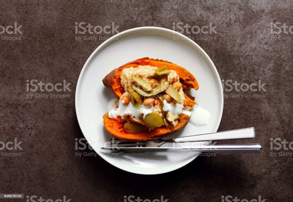 a dish of Sweet potato, baked in the oven, and Hummus with green olives and yogurt. Healthy tasty vegetarian food. stock photo