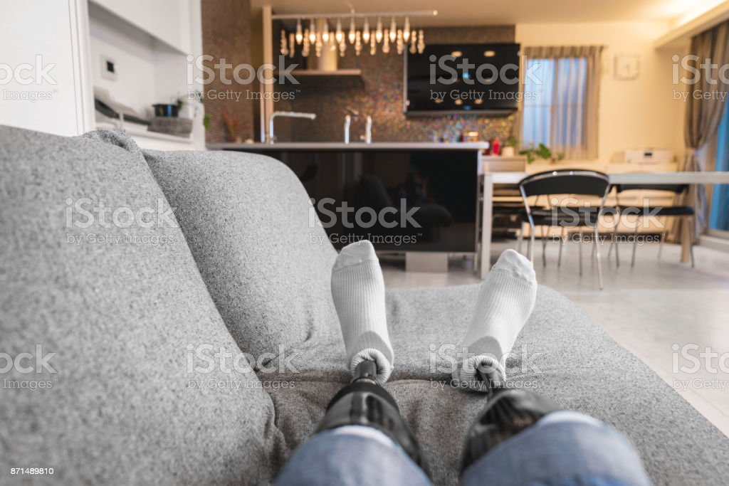 POV of a double amputee relaxing on the sofa stock photo