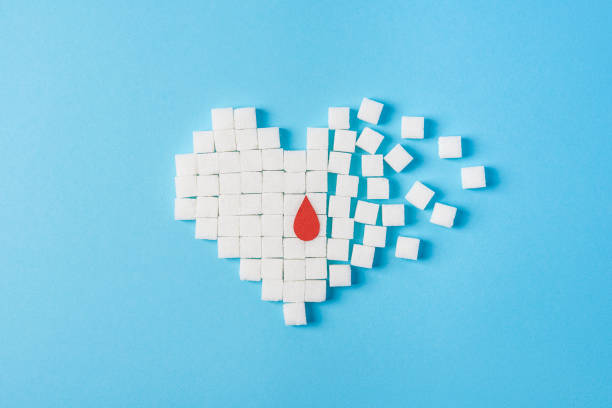 a drop of blood on broken heart made of pure white cubes of sugar isolated on blue background, world diabetes day - diabetic stock photos and pictures