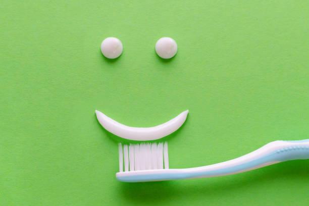ein Gesicht mit Lächeln aus weißer Zahnpasta, Zahnpflegekonzept, Zahnbürste auf grünem Hintergrund – Foto
