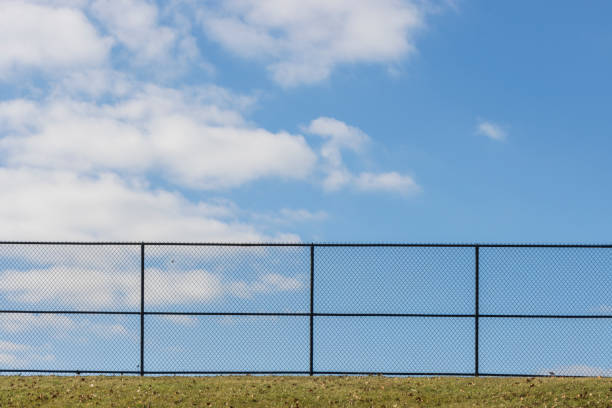 a fence on a blue sky day stock photo