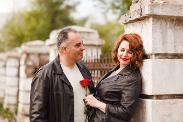 a fifty-year-old man looks gently at his wife. Happy middle-aged couple in summer outdoors stock photo