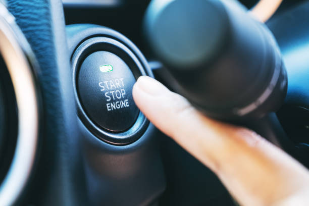 ein Finger drückt auf einen Start-Stopp-Motorknopf in einem Auto – Foto