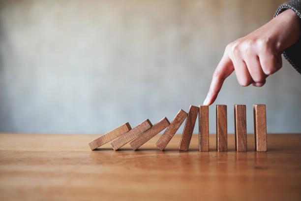 ein Finger versuchen, fallende Holz Dominosteine Blöcke für Business-Lösung Konzept zu stoppen – Foto