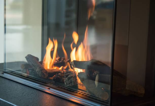 brennt ein feuer in einem kamin glas strahlt wärme - gaskamin stock-fotos und bilder