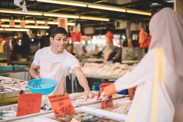 a fish vendor suggesting to his customer on the raw fish and selling at fish market a fish vendor suggesting to his customer on the raw fish and selling at fish market asian market stock pictures, royalty-free photos & images