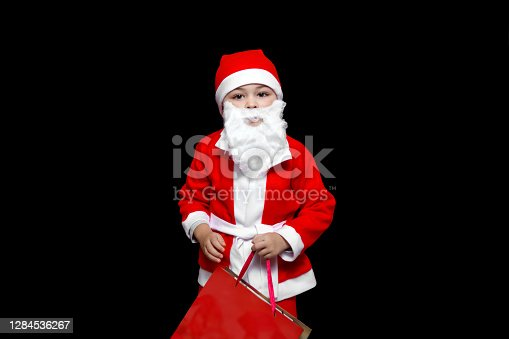 a five-year-old boy in a funny Santa Claus costume stands with a package of gifts. on a black isolated background.