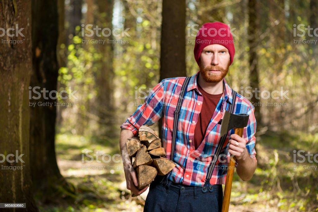 een boswachter met een baard draagt hout en een bijl, schieten in het bos - Royalty-free Alleen mannen Stockfoto