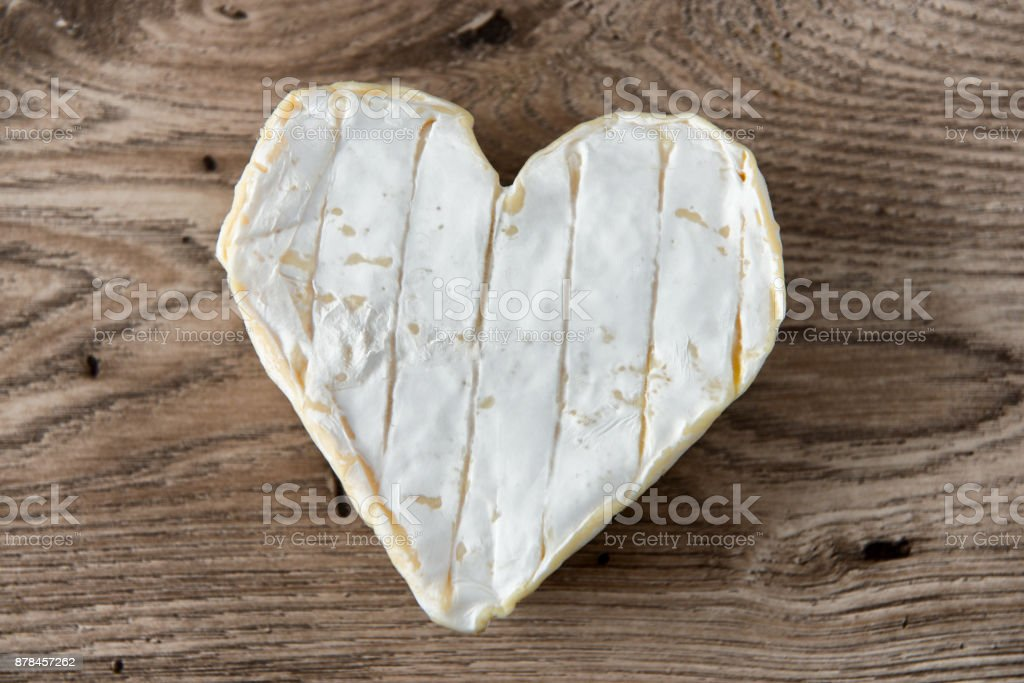 a French Neufchatel cheese shaped heart on a wooden table stock photo