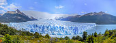 a front panoramic view of the Perito Moreno glacier over the Buenos Aires lake between the mountains, with the ice-fields at the background