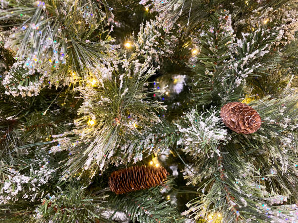 a frosted christmas tree holiday background with pine cones and gold lights stock photo