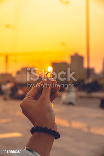 Horizontal color close-up image of woman looking at her engagement ring during beautiful sunset