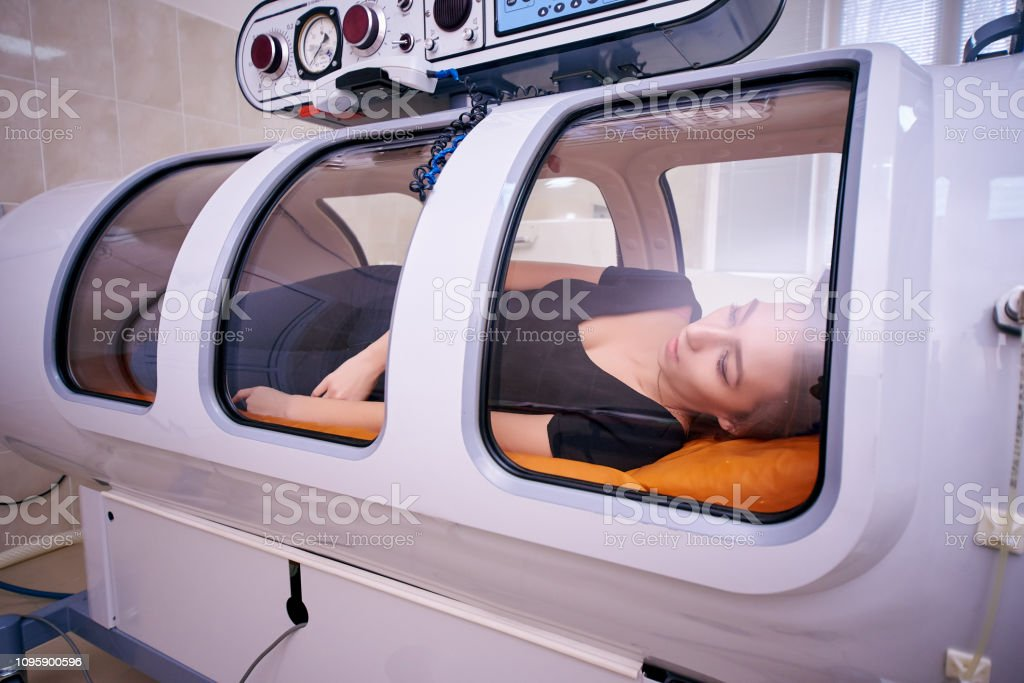 a girl in a black T-shirt lies in a hyperbaric chamber, oxygen therapy – zdjęcie