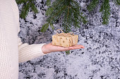 a girl in a white sweater holds a small gift in her palm on a snowy background
