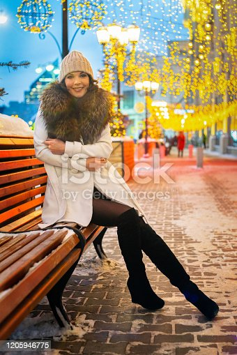 a girl sits in a park on a garland bench frost the new year is warming good building