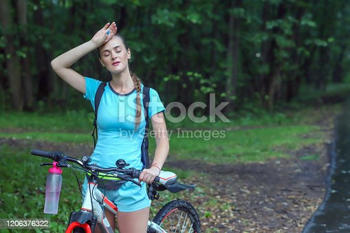 a girl with sportswear is standing in a park on a bicycle and raised her hand to her head because she was tired