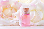 a glass bottle of essential oil and fresh rose flowers, selective focus
