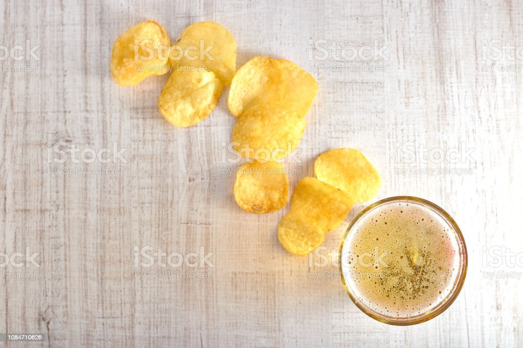 a glass of cold, light beer with chips scattered on the table. copy...