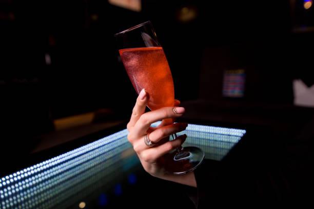 einem glas roten flüssigkeit in die hand einer frau - neon partylebensmittel stock-fotos und bilder