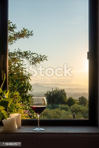 a glass of red wine stands in a window in Tuscany