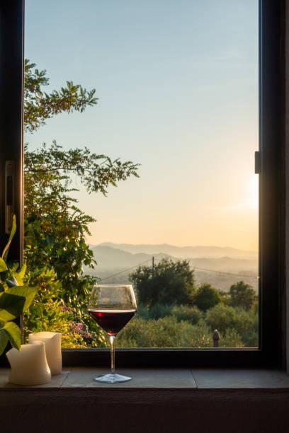 ein Glas Rotwein steht in einem Fenster in der Toskana – Foto