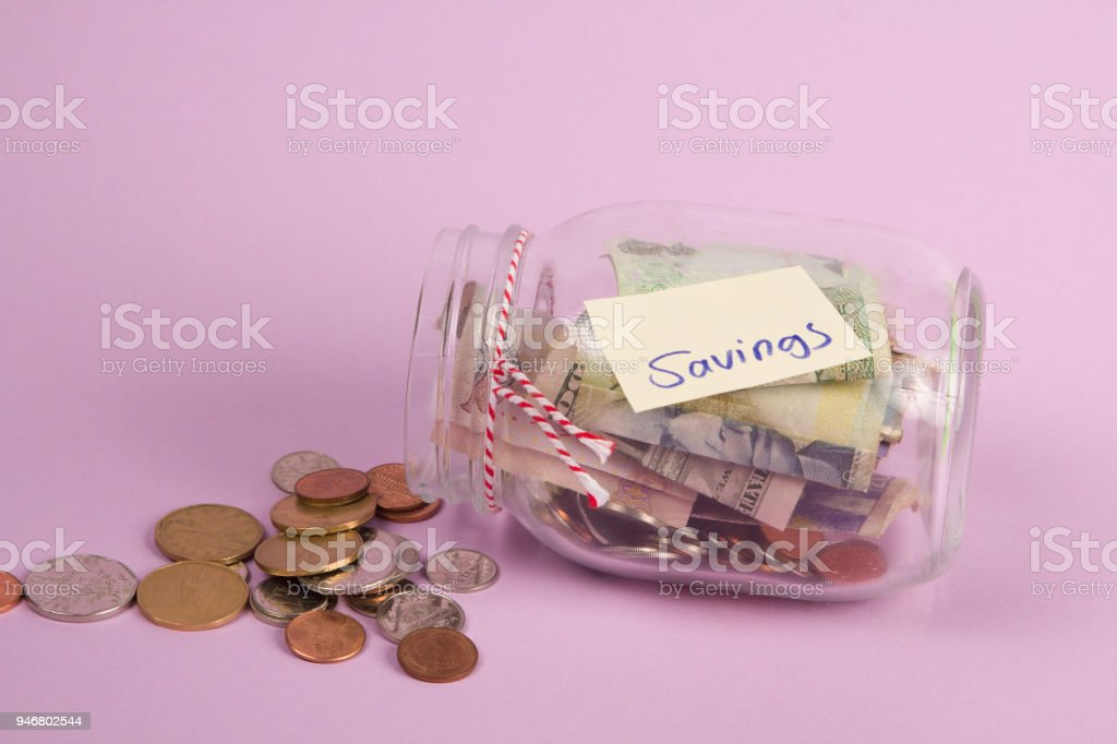 a glass savings jar filled with banknotes and coins stock photo