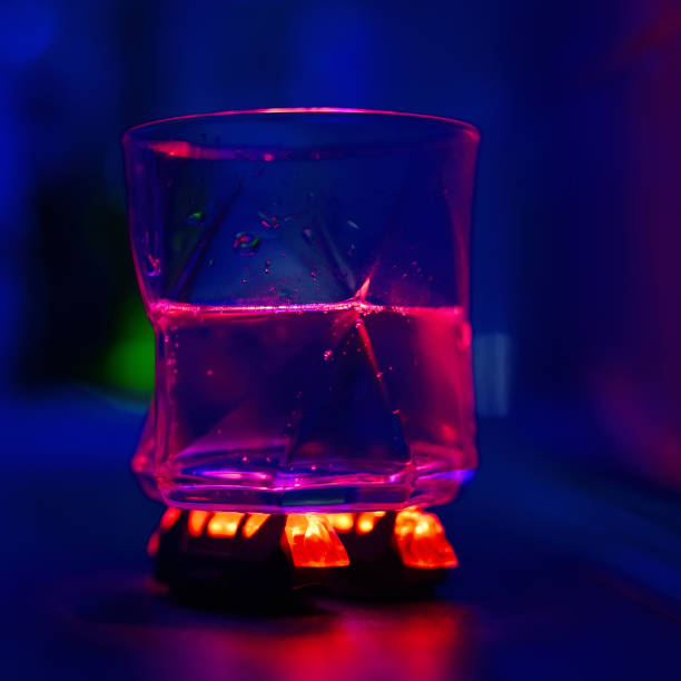 a glass with water on a red led lights stock photo