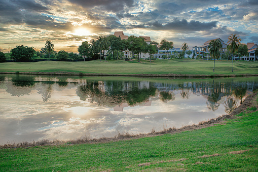 a golf course in melaka with sunset view in front of a lake with reflection