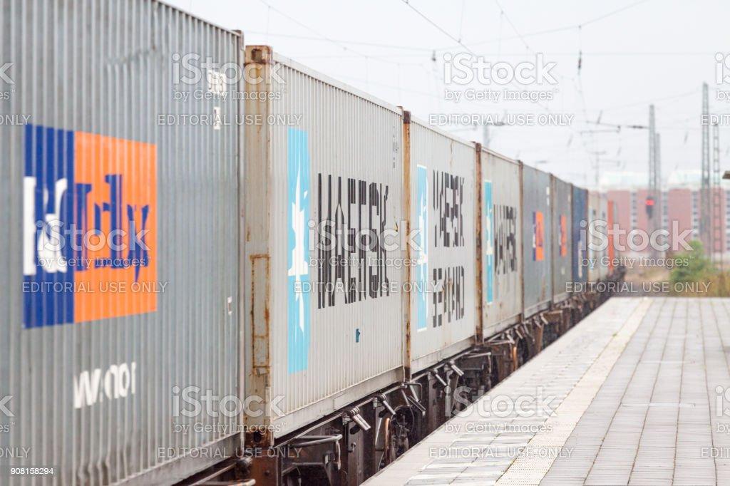 a good container train drives through trainstation.