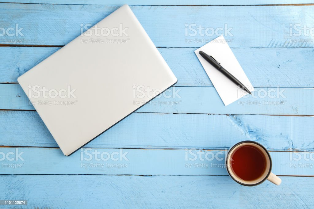 a gray laptop, a Cup of drink,a small paper notebook and a black pen...