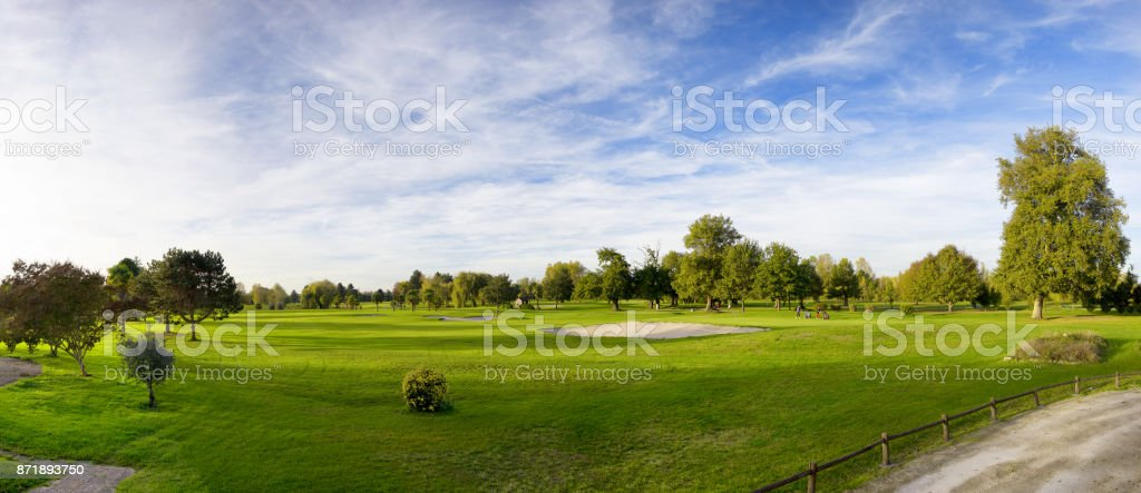 a green golf field and blue cloudy sky stock photo