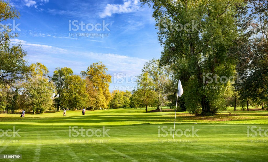 a green golf field and blue cloudy sky