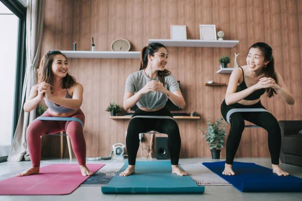 sekelompok teman wanita cina asia berlatih yoga di ruang tamu domestik bersama-sama - olahraga potret stok, foto, & gambar bebas royalti