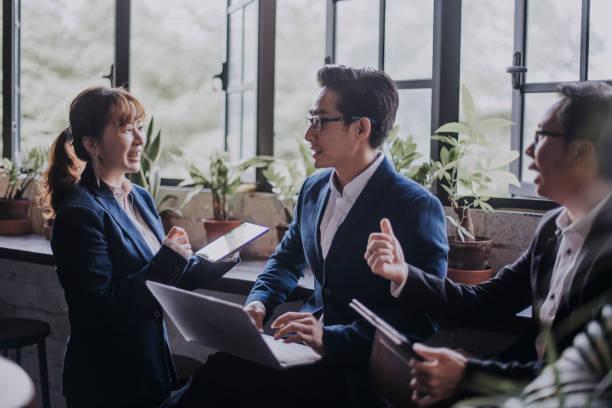 ラップトップとデジタルタブレットを使用してラウンジでコーヒーブレイク中に議論しているアジアの中国のホワイトカラー労働者のグループ - business malaysia ストックフォトと画像