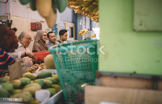 a group of asian customer in front of the fruit stall selecting and choosing fruits during weekend with their family members