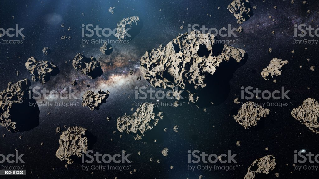 a group of asteroids in front of the galaxy stock photo
