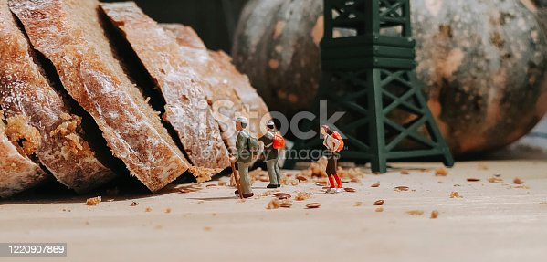 a group of figurine hikers at the loaf of bread , dough with tower