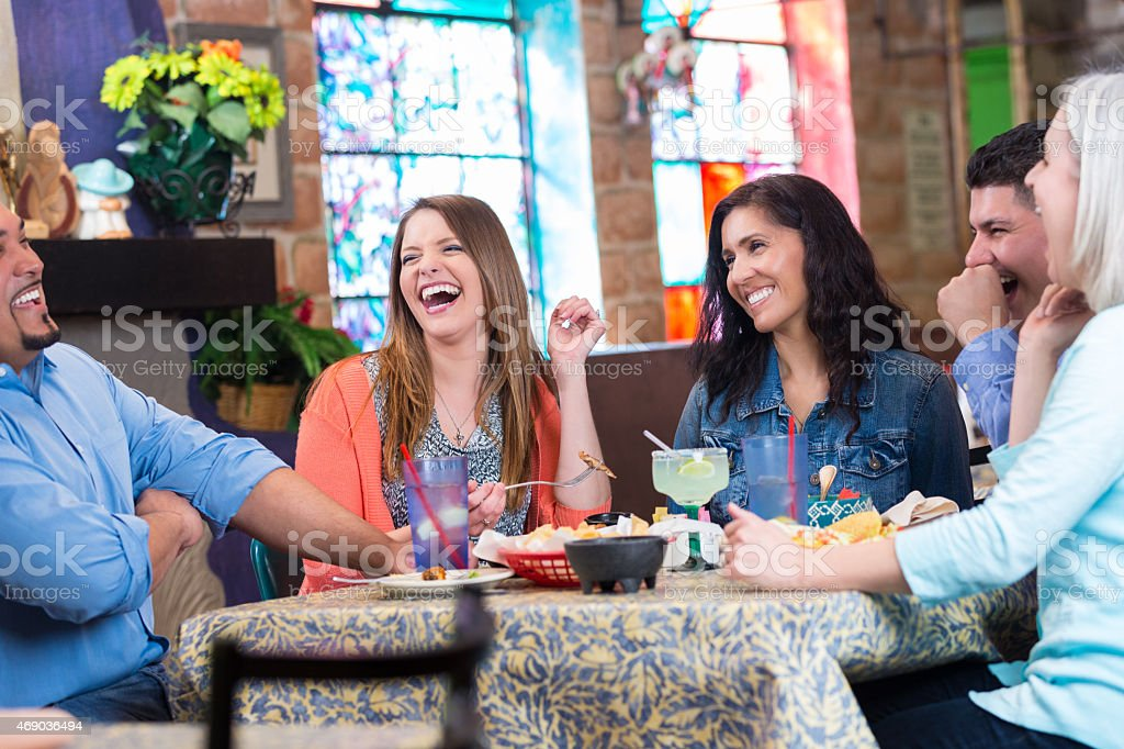 a group of friends laugh as they enjoy their Tex-mex stock photo