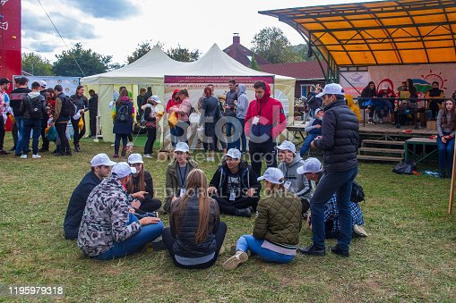 Adygea, Russia - September 21, 2019: a group of student volunteers sit on the grass at the Adyghe cheese festival