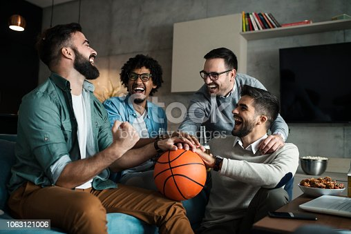 a group of young businessmen watch a basketball game on TV after work