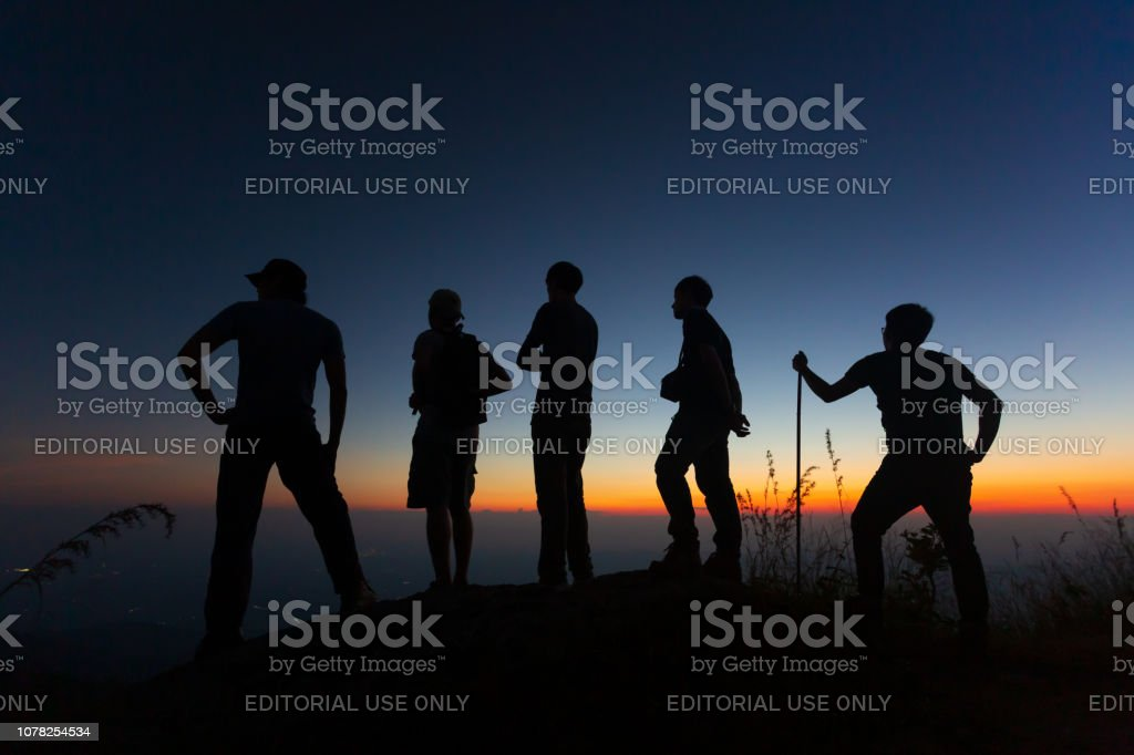 a group of young hikers are watching a sunset on a mountain. National Park in Thailand stock photo