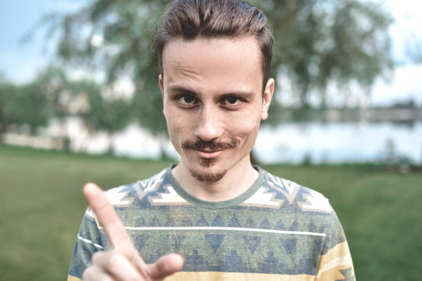 a guy with a sly expression on his face, shows a finger gesture, says do not try to deceive me - delude stock pictures, royalty-free photos & images