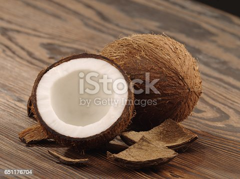 a half a coco lies on a wooden table