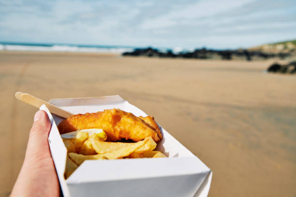 POV of a hand holding a box of Fish and Chips at Fistral Beach, Newquay, Cornwall on a bright sunny day. stock photo