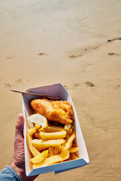 POV of a hand holding a box of Fish and Chips at the beach on a bright sunny day. stock photo